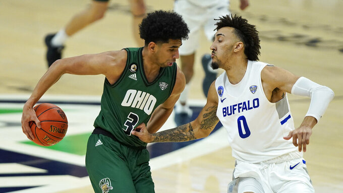Ohio's Ben Roderick (3) drives against Buffalo's David Nickelberry (0) during the first half of an NCAA college basketball game in the championship of the Mid-American Conference tournament, Saturday, March 13, 2021, in Cleveland. (AP Photo/Tony Dejak)