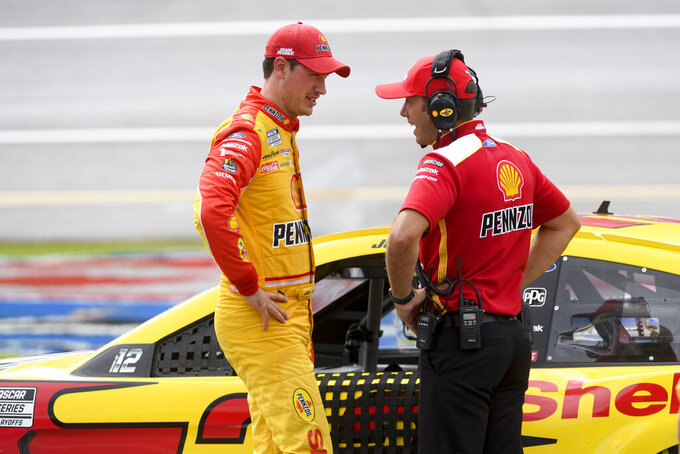 Joey Logano, left, talks with a team member as his car sits parked on pit row during a rain delay of a NASCAR Cup series auto race Monday, Oct. 4, 2021, in Talladega, Ala. (AP Photo/John Amis)