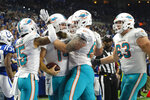 Miami Dolphins quarterback Ryan Fitzpatrick (14) is surrounded by teammates as he celebrates a touchdown against the Indianapolis Colts during the first half of an NFL football game in Indianapolis, Sunday, Nov. 10, 2019. (AP Photo/AJ Mast)