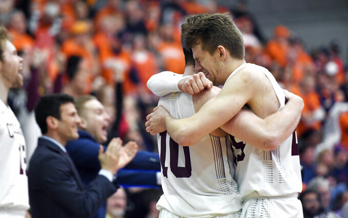 Colgate forward Rapolas Ivanauskas, right, hugs forward Will Rayman in the closing seconds of the team's NCAA college basketball game against Bucknell for the championship of the Patriot League men's tournament in Hamilton, N.Y., Wednesday, March 13, 2019. Colgate won 94-80. (AP Photo/Adrian Kraus)