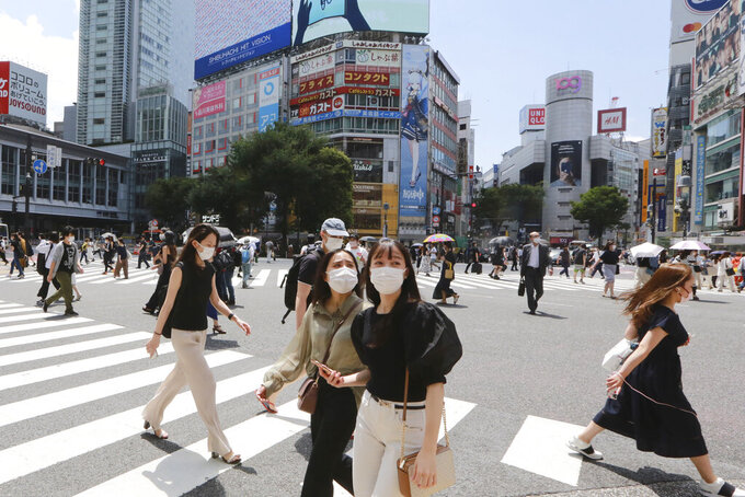 People wearing face masks to protect against the spread of the coronavirus walk on a street in Tokyo Wednesday, July 28, 2021. Tokyo Gov. Yuriko Koike on Wednesday urged younger people to cooperate with measures to bring down the high number of infections and get vaccinated, saying their activities are key to slowing the surge during the Olympics. On Tuesday, the Japanese capital reported 2,848 new cases, exceeding its previous record in January. (AP Photo/Koji Sasahara)
