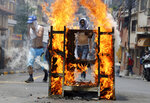 A demonstrator blocks a street during a protest demanding the resignation of President Juan Orlando Hernandez, in Tegucigalpa, Honduras, Sunday, Sept. 15, 2019. Hernández has suffered a credibility crisis since Honduras' Supreme Court cleared the way for his re-election despite a constitutional ban. His subsequent 2017 election win was marred by irregularities. (AP Photo/Elmer Martinez)