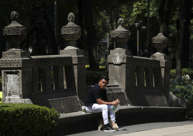 """A man takes a coffee break on an empty park bench along Paseo de la Reforma street in Mexico City, Tuesday, June 2, 2020, amid the new coronavirus pandemic. While the federal government's nationwide social distancing rule formally ended Monday, it is urging people in so-called """"red"""" zones to maintain most of those measures — and so many people are falling ill and dying each day that those zones cover nearly the whole country. (AP Photo/Fernando Llano)"""
