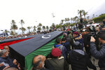 Mourners carry coffins during a funeral of military cadets in Tripoli, Libya, Sunday, Jan. 5, 2020. Health officials said the death toll from the airstrike climbed to at least 30 people, most of them students and over 30 others were wounded. The airstrike took place in the city's south late Saturday, an area which has seen heavy clashes in recent months. Forces based in eastern Libya and led by Gen. Khalifa Hifter have been fighting to seize the capital from the weak but U.N.-supported government. (AP Photo/Hazem Ahmed)