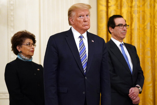 FILE - In this April 28, 2020 file photo President Donald Trump, along with Jovita Carranza, administrator of the Small Business Administration, and Treasury Secretary Steven Mnuchin listen during an event about the Paycheck Protection Program used to support small businesses during the coronavirus outbreak, in the East Room of the White House in Washington. The Small Business Administration is shouldering a massive relief effort for the nation's small businesses and their workers left reeling by the pandemic. The agency has committed to auditing every sizable emergency loan it approves. But six weeks after the $600 billion-plus program was launched, the agency has yet to make public the recipients of taxpayer aid.  (AP Photo/Evan Vucci)