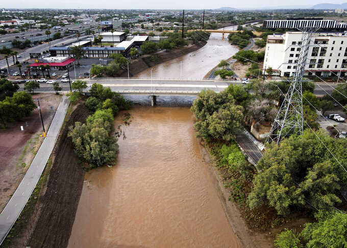 The Santa Cruz River flows through downtown Tucson, Ariz., Friday morning, July 23, 2021, swollen with rain from a large weather system. (Mamta Popat/Arizona Daily Star via AP)