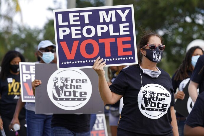 Supporters of restoring Florida felons' voting rights march to an early voting precinct, Saturday, Oct. 24, 2020, in Fort Lauderdale, Fla. The Florida Rights Restoration Coalition led marches to the polls in dozens of Florida counties. (AP Photo/Marta Lavandier)