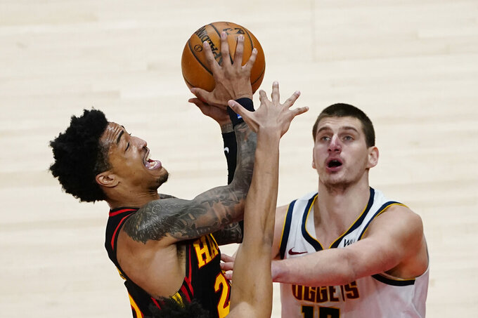 Atlanta Hawks forward John Collins, left,  goes in for a basket as Denver Nuggets center Nikola Jokic, right,  defends during the second half of an NBA basketball game Sunday, Feb. 21, 2021, in Atlanta. (AP Photo/John Bazemore)