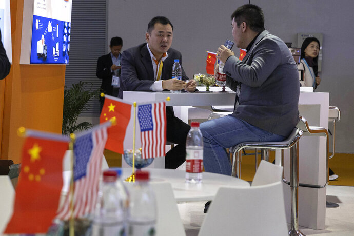 FILE - In this Nov. 6, 2019, file photo, visitors chat near American and Chinese flags displayed at a booth for an American company promoting environmental sensors during the China International Import Expo in Shanghai.  China pressed Washington on Thursday, Nov. 14, 2019 to roll back punitive tariffs in a tentative trade deal. (AP Photo/Ng Han Guan, FIle)