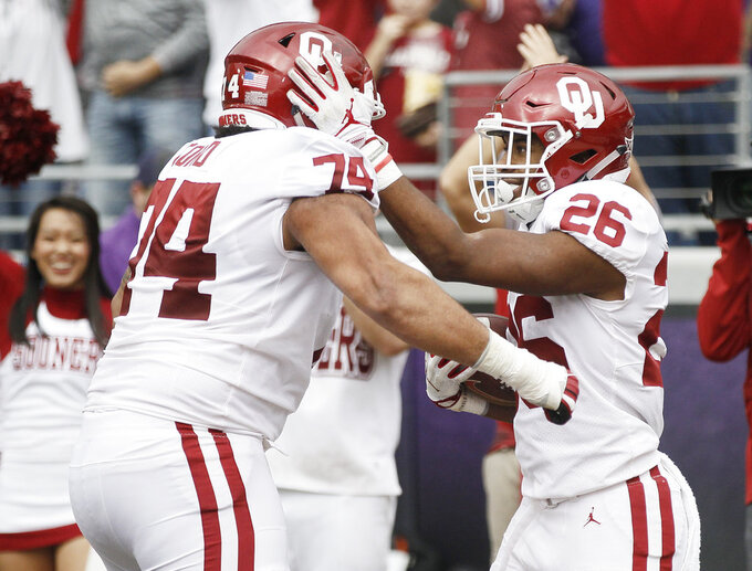 Oklahoma running back Kennedy Brooks (26) is congratulated by offensive lineman Cody Ford (74) after scoring a touchdown during the first half of an NCAA college football game against TCU, Saturday, Oct. 20, 2018, in Fort Worth, Texas. (AP Photo/Brandon Wade)