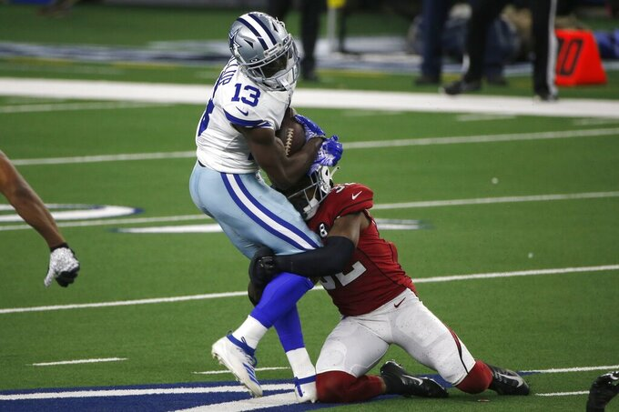 Dallas Cowboys wide receiver Michael Gallup (13) catches a pass for a first down as Arizona Cardinals safety Budda Baker (32) makes the stop in the first half of an NFL football game in Arlington, Texas, Monday, Oct. 19, 2020. (AP Photo/Michael Ainsworth)