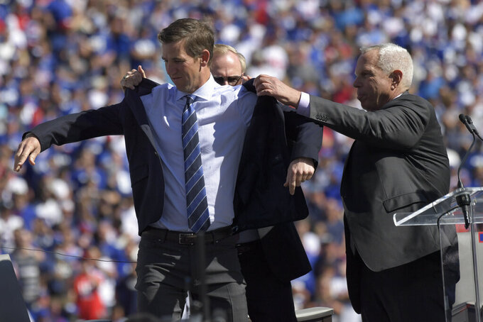 Former New York Giants quarterback Eli Manning is helped into a jacket while he attends a ceremony to retire his jersey number 10 and celebrate his tenure with the team during half-time of an NFL football game against the Atlanta Falcons, Sunday, Sept. 26, 2021, in East Rutherford, N.J. (AP Photo/Bill Kostroun)