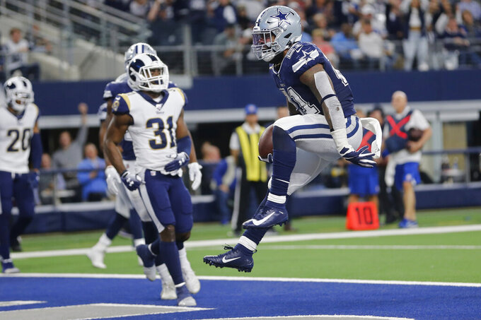 Dallas Cowboys running back Ezekiel Elliott (21) jumps into the end zone with a touchdown in front of Los Angeles Rams defensive back Darious Williams (31) in the first half an NFL football game in Arlington, Texas, Sunday, Dec. 15, 2019. (AP Photo/Michael Ainsworth)