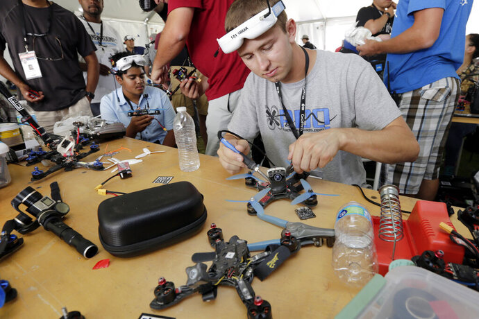 FILE - Competitor Tyler Brennan, a 22-year-old Air Force lieutenant from Colorado Springs, Colo., works on a quad copter before flying his racing drone through the obstacle course in the the National Drone Racing Championship on Governors Island, a former military installation in New York Harbor, Friday, Aug. 5, 2016, in New York. A major sports book is taking bets on aerial drone races. DraftKings said Friday it is taking bets for the championship this weekend of the Drone Racing League, in which pilots fly aerial drones in races against each other. (AP Photo/Richard Drew, File)