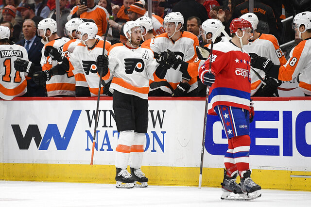 Philadelphia Flyers center Kevin Hayes, center, celebrates his goal, as Washington Capitals defenseman John Carlson, right, skates nearby during the second period of an NHL hockey game Wednesday, March 4, 2020, in Washington. (AP Photo/Nick Wass)