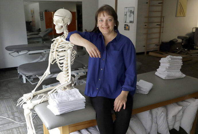 """In this Saturday, May 12, 2018, photo, April Oury, owner of Body Gears physical therapy center poses for a portrait with her instructional skeleton George, in Chicago. Oury started her physical therapy practice 14 years ago wanting to give all aspects of her business the same focus and attention to detail she gave patients, even when it came to choosing paint colors or an internet provider. She wouldn't do it that way again. """"There was not enough time in the day or the workweek to put that kind of effort into every single thing,"""" says Oury. (AP Photo/Charles Rex Arbogast)"""