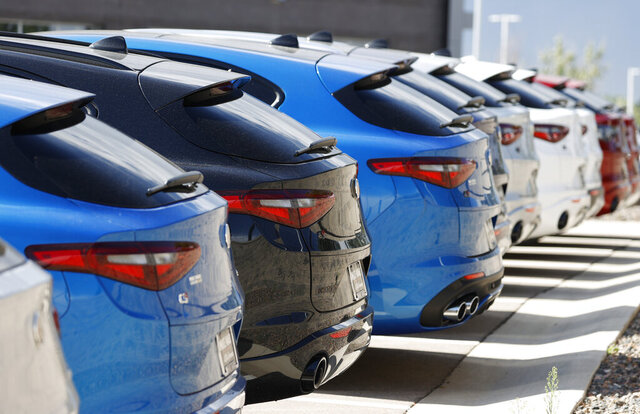 A long row of unsold 2020 Stelvio sports-utility vehicles sits at an Alfa Romeo dealership, Sunday, July 19, 2020, in Highlands Ranch, Colo. U.S. consumers took out more auto and student loans in October 2020, but cut back on credit card borrowing, a sign that they remain cautious about spending amid a spike in coronavirus cases. (AP Photo/David Zalubowski)