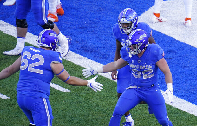 Air Force fullback Matthew Murla, front right, celebrates with quarterback Warren Bryan, back right, and guard Hawk Wimmer after running for a touchdown in the first half of an NCAA college football game against Boise State, Saturday Oct. 31, 2020, at Air Force Academy, Colo. (AP Photo/David Zalubowski)