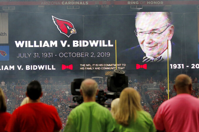 Fans pause for a moment of silence in memory of the late Arizona Cardinals owner William V. Bidwill prior to NFL football game against the Atlanta Falcons, Sunday, Oct. 13, 2019, in Glendale, Ariz. (AP Photo/Ross D. Franklin)