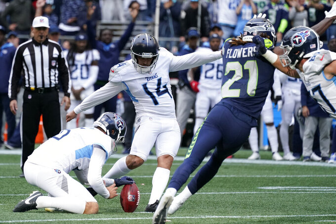 Tennessee Titans kicker Randy Bullock (14) kicks a field goal in overtime as Brett Kern holds to give the Titans a 33-30 win over the Seattle Seahawks in an NFL football game, Sunday, Sept. 19, 2021, in Seattle. (AP Photo/Elaine Thompson)
