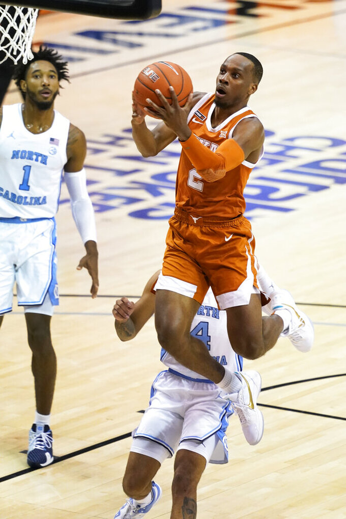 Texas guard Matt Coleman III (2) drives the ball to the basket past North Carolina guard R.J. Davis (4) and North Carolina guard Leaky Black (1) in the first half of an NCAA college basketball game for the championship of the Maui Invitational, Wednesday, Dec. 2, 2020, in Asheville, N.C. (AP Photo/Kathy Kmonicek)