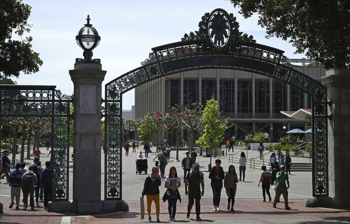 FILE - In this May 10, 2018, file photo, students walk past Sather Gate on the University of California at Berkeley campus in Berkeley, Calif. A California state audit found that the University of California wrongly admitted at least 64 wealthy students over the past six years as