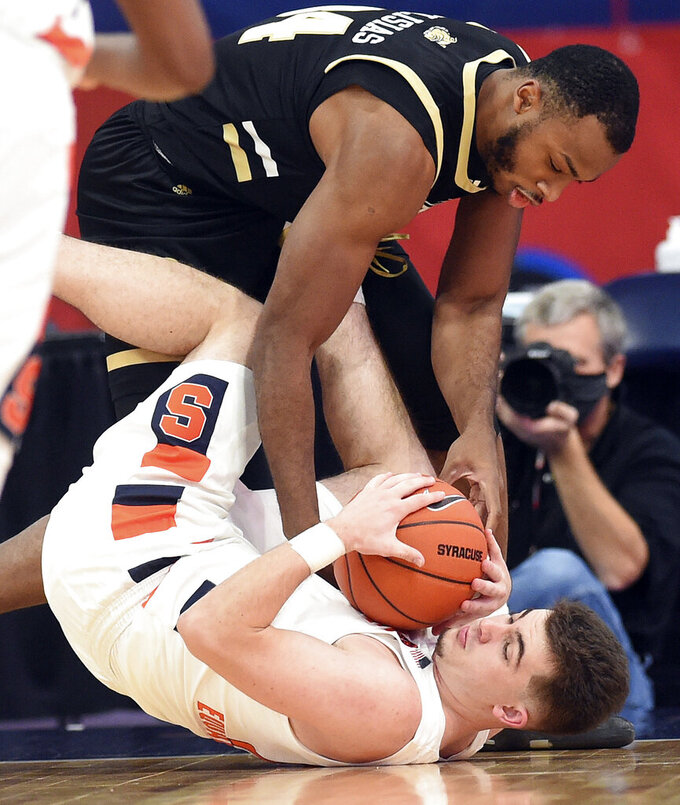 Bryant forward Hall Elisias (34) and Syracuse guard Joseph Girard III (11) battle for the ball during the first half of an NCAA college basketball game, Friday, Nov. 27, 2020, in Syracuse, N.Y. (Dennis Nett/The Post-Standard via AP)