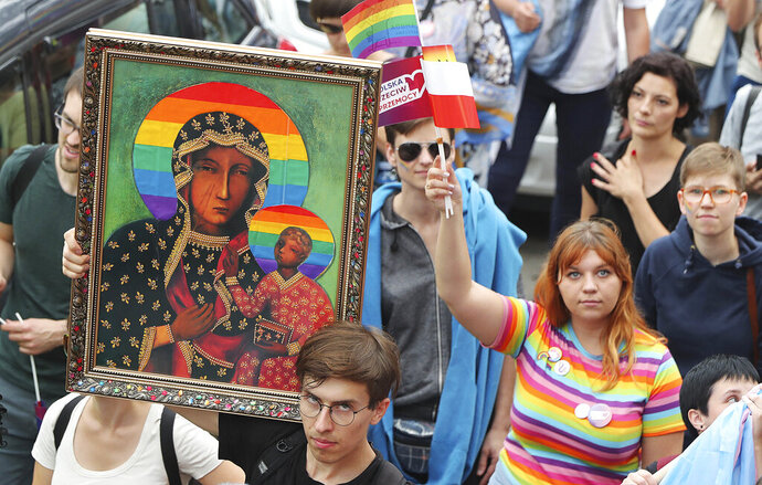 In this Aug. 10, 2019, photo, people take part in a gay pride parade holding up an image of Madonna and Baby Jesus that has offended many Catholics in Plock, Poland. The image was made by an activist in protest. (AP Photo/Czarek Sokolowski)