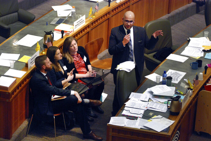 In this Thursday, March 7, 2019 photo, New Mexico state Rep. Javier Martinez of Albuquerque, right, rallies support for a bill to authorize recreational marijuana consumption and sales through state-owned stores in Santa Fe, N.M. New Mexico took a step toward legalizing recreational marijuana when its House approved a bill that would allow state-run stores and require customers to carry a receipt with their cannabis or face penalties. The measure, narrowly approved Thursday, March 7, 2019, following a late-night floor debate, mixes major provisions of a Republican-backed Senate bill that emphasizes aggressive regulation with a draft by Democrats concerned about the U.S. war on drugs. (AP Photo/Morgan Lee)