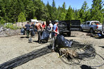 This May 7, 2019, photo released by Cannabis Removal on Public Lands (CROP) Project, workers from Trinity County RCD, Hayfork Watershed Center, Cannabis for Conservation, Watershed Stewards Program, and Dell' Arte International prepare trash to be air lifted for disposal from a trespass grow complex where nearly 9,000 illegally cultivated cannabis plants were found in the Shasta-Trinity National Forest, in Calif. Authorities allege members of an international drug trafficking ring set up camp at the site months earlier. Along with the hundreds of pounds of harvested marijuana, they also found thousands of pounds of trash and more than three miles (4.8 kilometers) of plastic irrigation piping, according to the Trinity County Sheriff's Office. (Jackee Riccio/CROP Project via AP)
