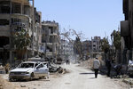 Syrians walk through destruction in the town of Douma, the site of a suspected chemical weapons attack, near Damascus, Syria, Monday, April 16, 2018. Faisal Mekdad, Syria's deputy foreign minister, said on Monday that his country is