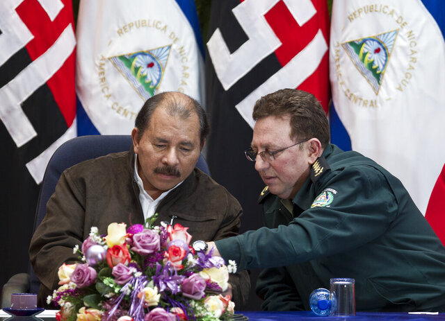 FILE - In this Dec 5, 2012 file photo, Nicaragua's President Daniel Ortega, left, and Nicaragua's Army Commander Gen. Julio Cesar Aviles Castillo speak during the closing ceremony of an annual defense course at the