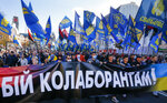 People carry flags of right-wing party Svoboda and a banner reading