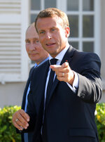 French President Emmanuel Macron, right, gestures with Russian President Vladimir Putin ahead of their meeting at the fort of Bregancon in Bormes-les-Mimosas, southern France, Monday Aug. 19, 2019. French President Emmanuel Macron and Russian President Vladimir Putin are meeting to discuss the world's major crises, including Ukraine, Iran and Syria, and try to improve Moscow's relations with the European Union. (Alexei Druzhinin, Sputnik, Kremlin Pool Photo via AP)