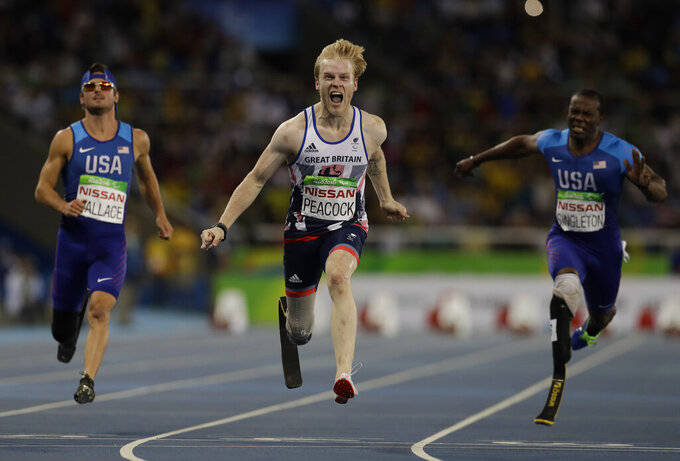 """FILE - In this Sept. 9, 2016, file photo, Britain's Jonnie Peacock, center, celebrates crossing the finish line first, followed by United States' Jerome Singleton, right, and Jarryd Wallace during the men's final 100-meter T44 athletics event at the Paralympic Games in Rio de Janeiro, Brazil. Peacock is among several Paralympic athletes who are profiled in the Nexflix documentary """"Rising Phoenix"""" that will be released in 190 countries on Wednesday, Aug. 26, 2020. (AP Photo/Leo Correa, File)"""