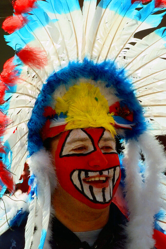 FILE - Cleveland Indians fan Mike Margevicus waits to enter Jacobs Field for the team's home opener in Cleveland, in this Friday, April 10, 1998, file photo. While moving forward with a plan to change their name, the Cleveland Indians said they will not permit fans inside Progressive Field wearing headdresses or inappropriate face paint. The team announced the new guidelines on Wednesday, March 31, 2021, in advance of Monday's home opener against Detroit. (AP Photo/Mark Duncan, File)