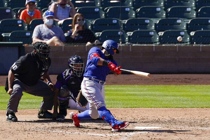 Texas Rangers' Rougned Odor (12) hits a home run during the sixth inning of a spring training baseball game against the Colorado Rockies Monday, March 22, 2021, in Scottsdale, Ariz. (AP Photo/Ashley Landis)