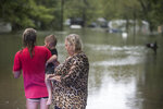 Tiffany Loden, left, holds her son, Braxton, as she and Linda Anson stand at the edge of their flooded neighborhood inundated by rains from Tropical Depression Imelda on Thursday, Sept. 19, 2019, in Spendora. Her house, where she has lived for just two weeks, is the one with the white roof. (Brett Coomer/Houston Chronicle via AP)