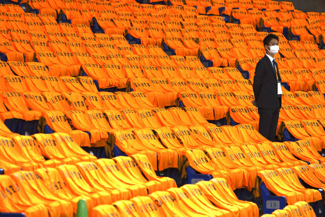 A man stands at the empty seats with orange color jerseys prior to an opening baseball game between the Yomiuri Giants and the Hanshin Tigers at Tokyo Dome in Tokyo Friday, June 19, 2020. Japan's professional baseball regular season will be kicked off Friday without fans in attendance because of the threat of the spreading coronavirus. (AP Photo/Eugene Hoshiko)