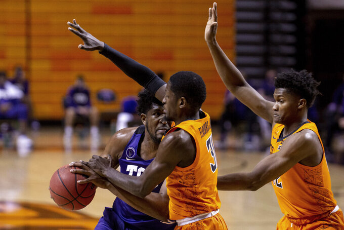 Oklahoma State guard Ferron Flavors Jr. (31) and Oklahoma State forward Matthew-Alexander Moncrieffe (12) guard TCU center Kevin Samuel (21) during the first half of the NCAA college basketball game in Stillwater, Okla., Wednesday, Dec. 16, 2020. (AP Photo/Mitch Alcala)