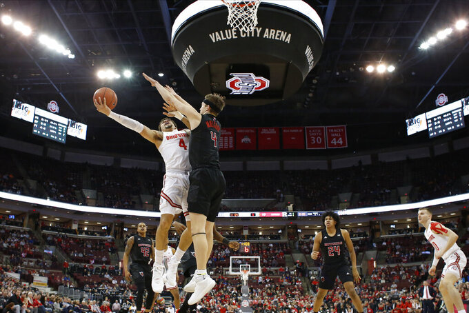 Ohio State's Duane Washington, left, tries to shoot over Rutgers' Paul Mulcahy during the first half of an NCAA college basketball game Wednesday, Feb. 12, 2020, in Columbus, Ohio. Ohio State beat Rutgers 72-66. (AP Photo/Jay LaPrete)