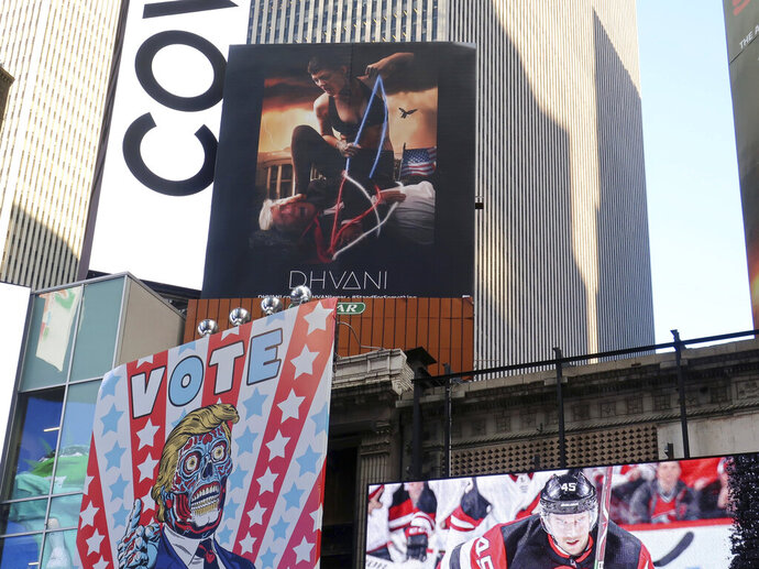 A billboard in New York City's Time Square depicts President Donald Trump being hogtied by a woman clad in athletic wear on Friday, Oct. 18, 2019. The The 30-foot-high billboard is part of an advertising campaign by Dhvani, a Portland-based clothing company. CEO of Dhvani Avi Brown told The Associated Press the billboard was intended to be a comment on the Trump administration's changes to the Title X family planning program blocking federal funding for health providers who refer patients for abortions. (AP Photo/Ted Shaffrey)