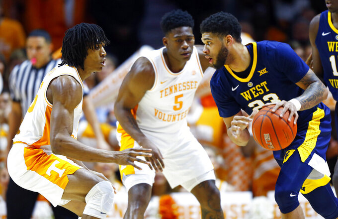 West Virginia forward Esa Ahmad (23) drives as he's defended by Tennessee forward Yves Pons (35) and guard Admiral Schofield (5) in the first half of an NCAA college basketball game Saturday, Jan. 26, 2019, in Knoxville, Tenn. (AP Photo/Wade Payne)