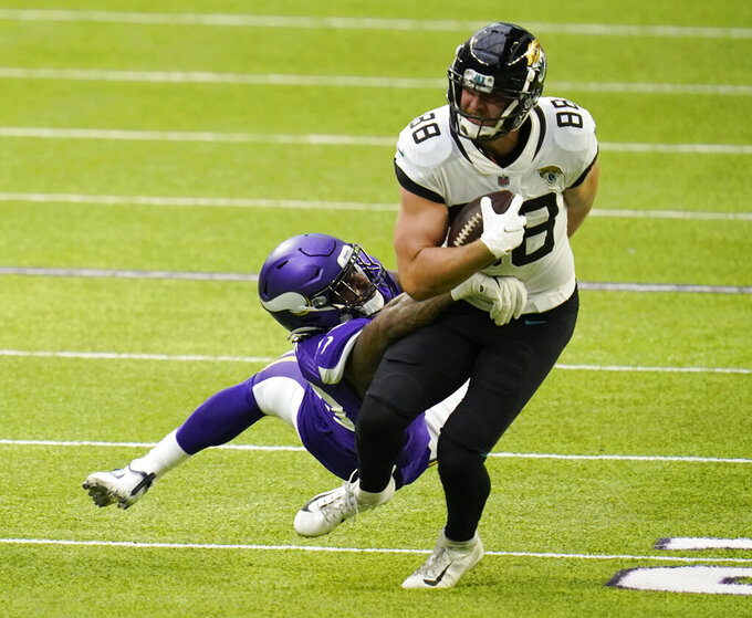 Jacksonville Jaguars tight end Tyler Eifert (88) tries to break a tackle by Minnesota Vikings linebacker Todd Davis (40) during the first half of an NFL football game, Sunday, Dec. 6, 2020, in Minneapolis. (AP Photo/Jim Mone)