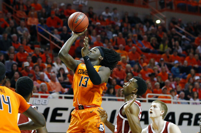 Oklahoma State guard Isaac Likekele (13) shoots in front of Oklahoma guard Jamal Bieniemy (24) and forward Brady Manek, right, in the first half of an NCAA college basketball game in Stillwater, Okla., Saturday, Feb. 22, 2020. (AP Photo/Sue Ogrocki)