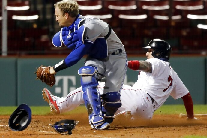 Boston Red Sox's Christian Vazquez (7) scores the winning run next to Toronto Blue Jays' Caleb Joseph during the ninth inning of a baseball game Saturday, Sept. 5, 2020, in Boston. (AP Photo/Michael Dwyer)