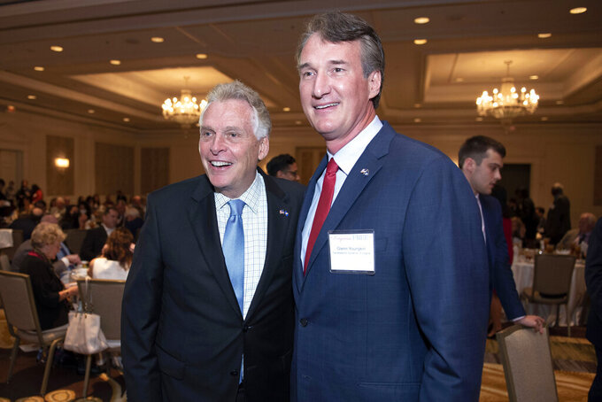 FILE - Virginia gubernatorial candidates, Democrat Terry McAuliffe left, and Republican Glenn Youngkin, pose for a photo, during the Virginia FREE leadership luncheon, in McLean, Va.  McAuliffe and Youngkin are set to square off in Virginia's first gubernatorial debate of the general election season, Thursday, Sept. 16. The race is being closely watched as a possible indicator of voter sentiment heading into the 2022 national midterm elections.    (AP Photo/Cliff Owen, File)