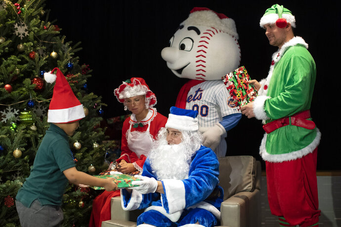 New York Mets outfielder Brandon Nimmo, center, dressed as Santa, his wife Chelsea Bradley, left, as Mrs. Claus, infielder J.D. Davis, right, dressed as an Elf and Mr. Met hand out gifts to local children during the team's annual Kids Holiday Party, Wednesday, Dec. 4, 2019, in New York. (AP Photo/Mary Altaffer)