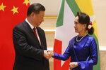 Myanmar's leader Aung San Suu Kyi, right, shakes hands with Chinese President Xi Jinping during their meeting at the Presidential Palace in Naypyitaw, Myanmar, Friday, Jan. 17, 2020. (AP Photo/Aung Shine Oo)