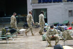 Members of the Louisiana National Guard prepare beds in a shelter ahead of Hurricane Delta, Friday, Oct. 9, 2020, in Lake Charles, La. Forecasters said Delta — the 25th named storm of an unprecedented Atlantic hurricane season — would likely crash ashore Friday evening somewhere on southwest Louisiana's coast. (AP Photo/Gerald Herbrt)